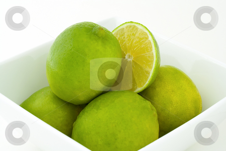 Green limes in a bowl stock photo, Whole green limes and a half of a lime in white porcelain bowl. Isolated on white background. by Natalia Banegas