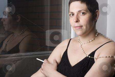 Women in evening dress stock photo, Twenty something women in evening dress with unlit cigarette by Yann Poirier