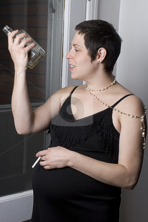 Pregnant women drinking stock photo, Twenty something women in evening dress with unlit cigarette looking at an empty hard liquor bottle by Yann Poirier