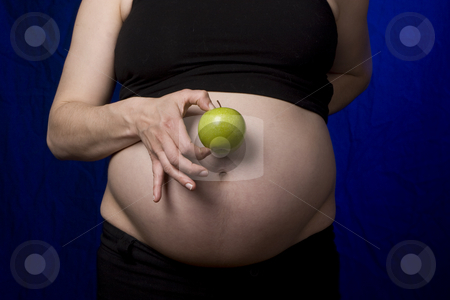 Pregnant belly and apple stock photo, Pregnant women holding a green apple to her belly by Yann Poirier