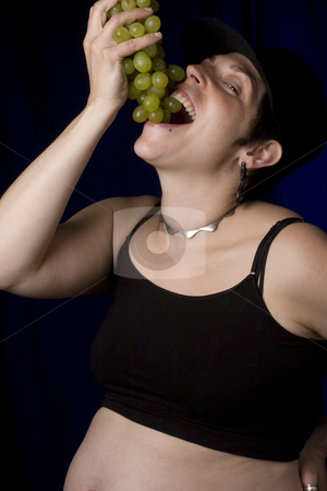 Eating grapes stock photo, Twenty something pregnant women with boyish look eating green grapes by Yann Poirier