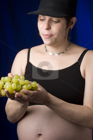Choosing grapes stock photo, Pregnant women choosing green grapes by Yann Poirier