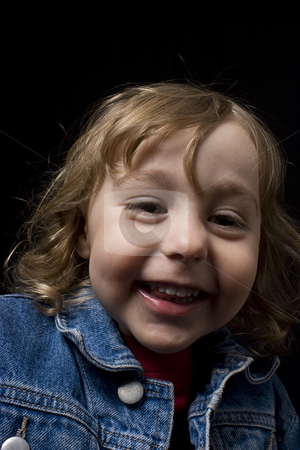 Toddler laughing stock photo, Portrait of a two year old boy wearing a jean jacket laughing by Yann Poirier