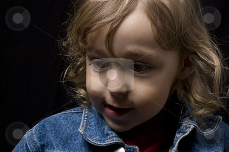 Toddler looking down stock photo, Portrait of a two year old boy wearing a jean jacket looking down to the left by Yann Poirier
