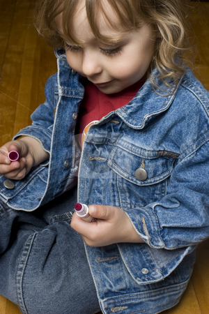 Toddler with marker stock photo, Portrait of a two year old boy wearing a jean jacket with great big smile playing with pink marker sitting on a wood floor by Yann Poirier