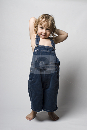 Toddle in overall acting shy stock photo, Two year old toddler wearing a jean overall acting shy by Yann Poirier