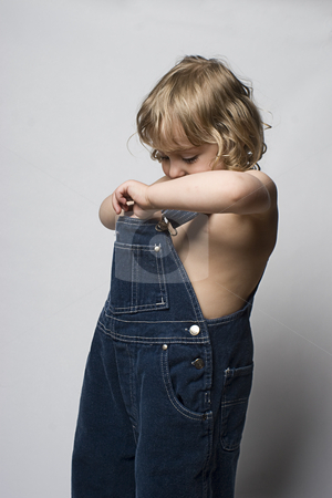 Toddle in overall searching stock photo, Two year old toddler searching in his jean overall by Yann Poirier