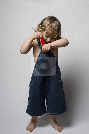 Toddle in overall and his harmonica stock photo, Two year old toddler putting aways his harmonica in his jean overall by Yann Poirier