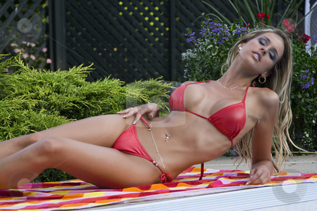 Women in bikini stock photo, Twenty something woment lounging by the side of the pool in a red binikin by Yann Poirier