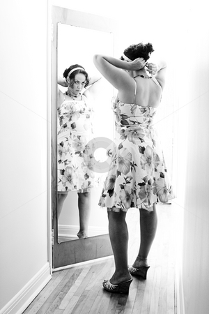 Woman in front of mirror stock photo, Twenty something women adjusting hand band in front of a mirror attach to a door by Yann Poirier