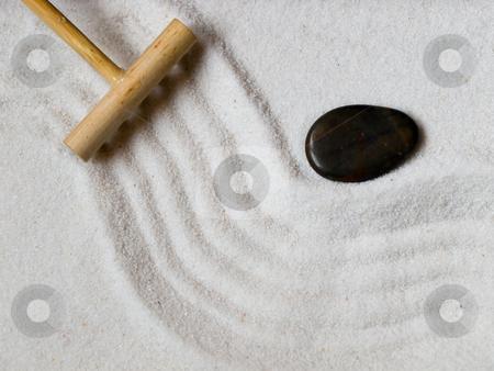 Japanese zen  garden stock photo, Close-up of a a Japanese zen garden with a wooden rake and a black stone. by FEL Yannick