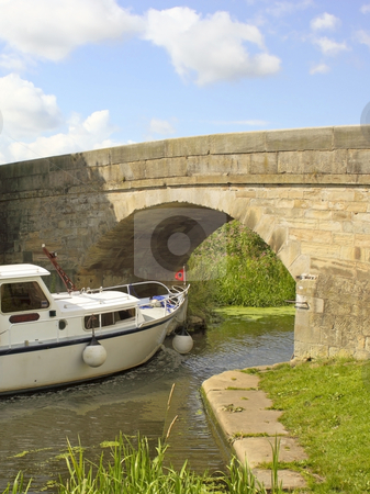 Bridge ahead stock photo, A leisure boat approaching a bridge on a canal waterway in summer by Mike Smith