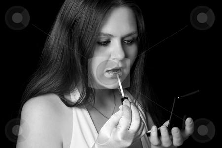 Teenager applying makeup stock photo, Teenage girl applying lip gloss by Yann Poirier