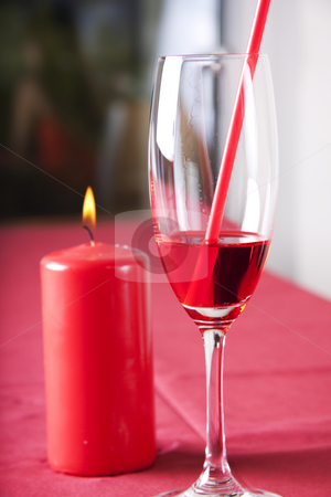 Red cocktail and candle stock photo, Red cocktail in a glass with a straw and a red candle by Daniel Kafer