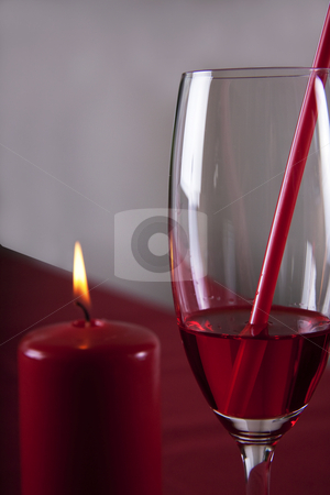 Red cocktail and a red candle stock photo, Red cocktail in a glass with a straw and a bottle by Daniel Kafer