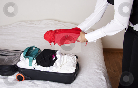 Woman packing a suitcase stock photo, Full suitcase on a bed and a woman adding a red dress by Daniel Kafer