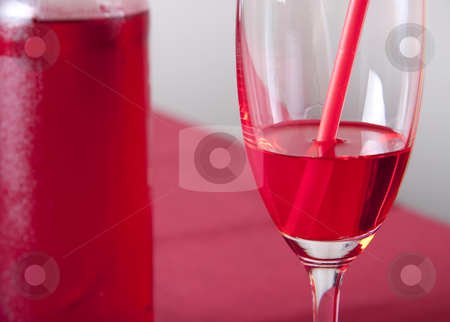 Red cocktail stock photo, Red cocktail in a glass with a straw and a bottle by Daniel Kafer