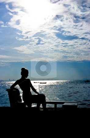 Silhouette stock photo, Silhouette of a young woman sitting at the ocean by Dmitry Rostovtsev