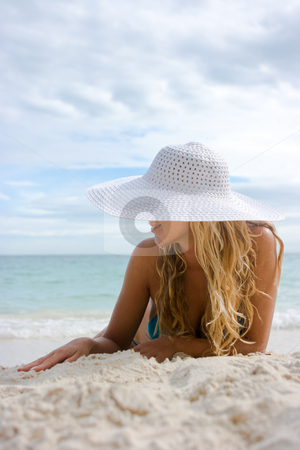 Blonde in white hat on the beach stock photo, Beautiful blonde lying on white sand beach in hat by Dmitry Rostovtsev
