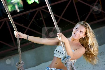 Lady on swings stock photo, Blonde lady swinging on rope swings on the beach by Dmitry Rostovtsev