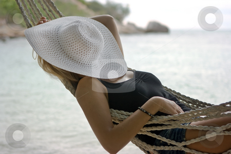 Relaxing stock photo, Blond girl lying in the hammock on the seashore by Dmitry Rostovtsev