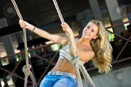Swinging stock photo, Cute blond girl swinging on rope swings by Dmitry Rostovtsev