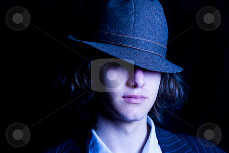 Teen with hat  stock photo, Male teenager with a hat tipped over the eyes by Yann Poirier