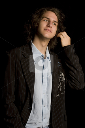 Brushing back hair stock photo, Male teenager wearing a suit, brushing back his hair by Yann Poirier