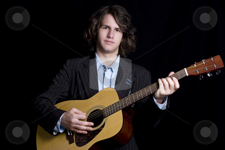 Teen Guitar player stock photo, Male teenager folk guitar player with blank expression by Yann Poirier