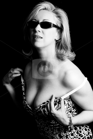 Dressing Fashionyta stock photo, Women in her early fifties wearing sunglass readjusting her dress by Yann Poirier