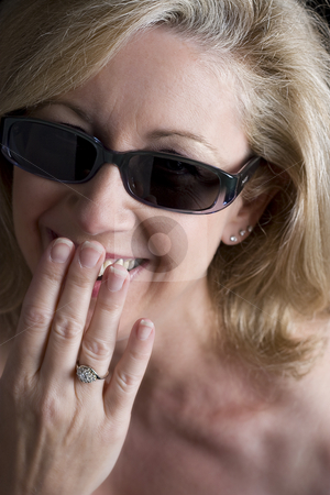 Fashionyta having a shy laugh stock photo, Women in her early fifties hidding a shy laugh behind her hand by Yann Poirier
