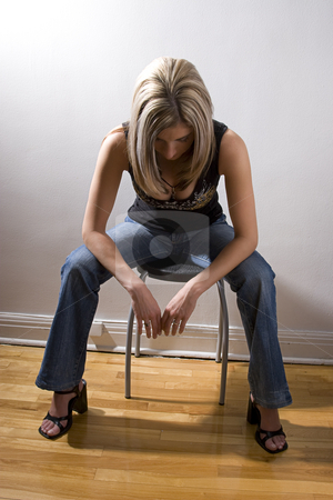 Looking down stock photo, Thirty something women dress in rocker style, sitting on stool looking at the floor by Yann Poirier
