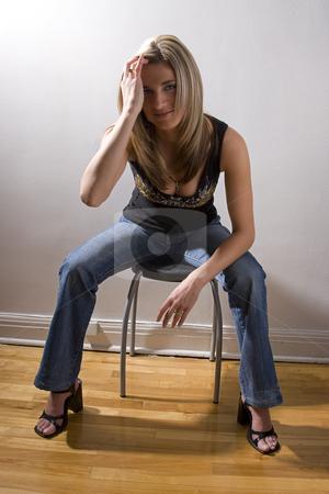 Brushing back hair stock photo, Thirty something women dress in rocker style sitting on a stool, brushing back her hair by Yann Poirier