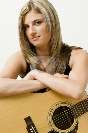 Musician stock photo, Thirty something women leaning on a accoustical guitar by Yann Poirier