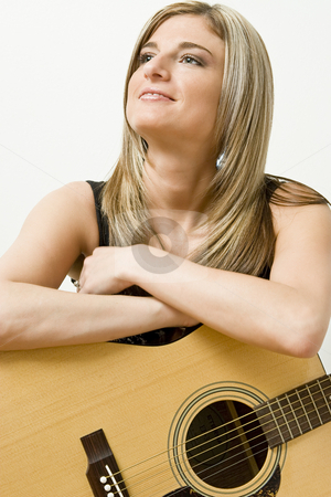 Women and guitar stock photo, Thirty something women leaning on a accoustical guitar by Yann Poirier