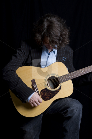 Bend over laughing stock photo, Male teenager folk guitar player bend over laughing by Yann Poirier