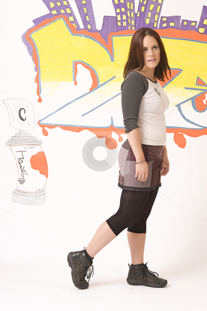 Walking in front of a graffiti stock photo, Teen girl walking in front of a graffiti by Yann Poirier