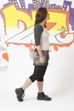 Walking in front of a graffiti stock photo, Teen girl walking in front of a graffiti looking into the distance by Yann Poirier