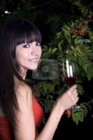Woman outside with red drink stock photo, Latina woman outside with green plants in the background with a red drink and a red drink by Daniel Kafer