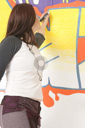 Writting on wall stock photo, Teen girl drawing a graffiti on a wall by Yann Poirier