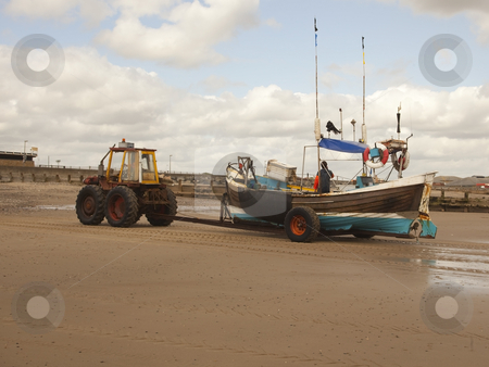 Tractor towing fishing boat stock photo, A tractor towing a fishing boat home on a beach in summer by Mike Smith