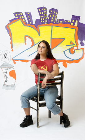 Day dreaming stock photo, Young women day dreaming sitting on a ruff up chair in front of a graffiti background by Yann Poirier