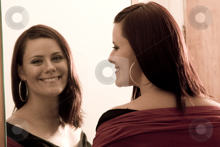 Smiling in reflecting stock photo, Young women looking at her reflection in a mirror with a big smile by Yann Poirier