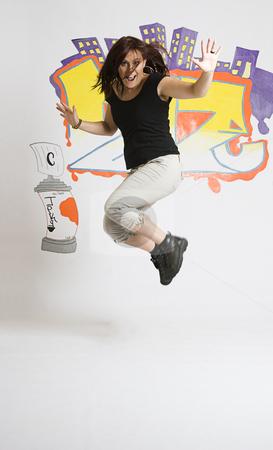 Break dancing girl jumping stock photo, Late twenties break dancing girl in the middle of a jump by Yann Poirier