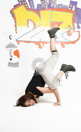 Women breakdancing stock photo, Young women in the middle of a breakdancing move balancing on her head done in front of a graffiti background by Yann Poirier