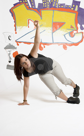Women breakdancing stock photo, Young women in the middle of a breakdancing move balancing on her hand done in front of a graffiti background by Yann Poirier