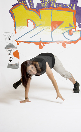 Women breakdancing stock photo, Young women in the middle of a breakdancing move balancing on her hands done in front of a graffiti background by Yann Poirier