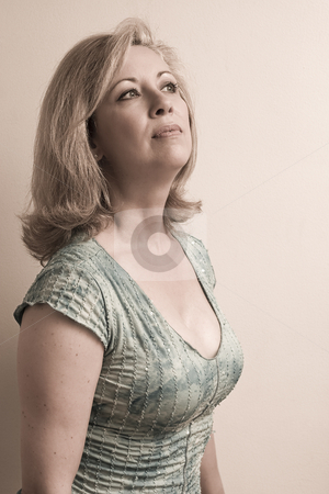 Looking up stock photo, Women in her early fifties leaning on wall looking up by Yann Poirier