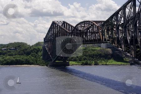 Metal bridge stock photo, Quebec old metal bridge with sail boat passing under by Yann Poirier