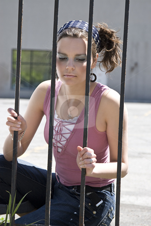 Girl behind fence stock photo, Yound women with sad expression behind a fence made out of iron bars by Yann Poirier